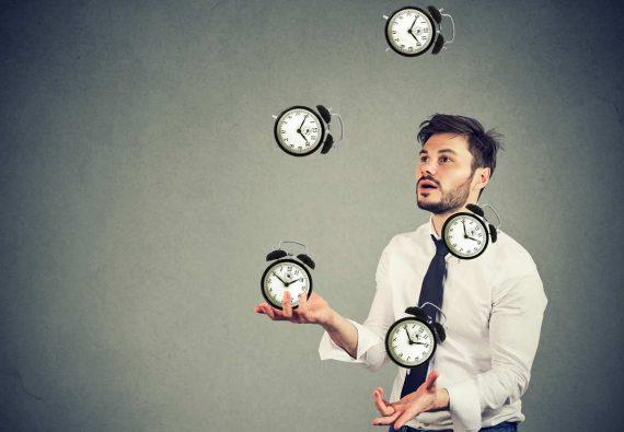 Junger Mann mit struppigem Haar und Krawatte jongliert Uhren