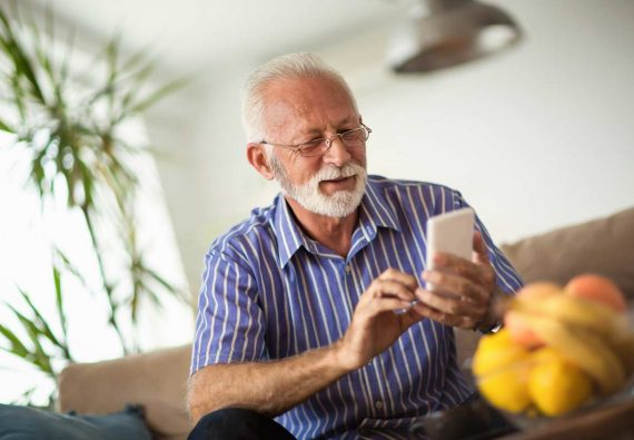 Älterer Herr sitzt auf Couch und schaut lächelnd in sein Smartphone